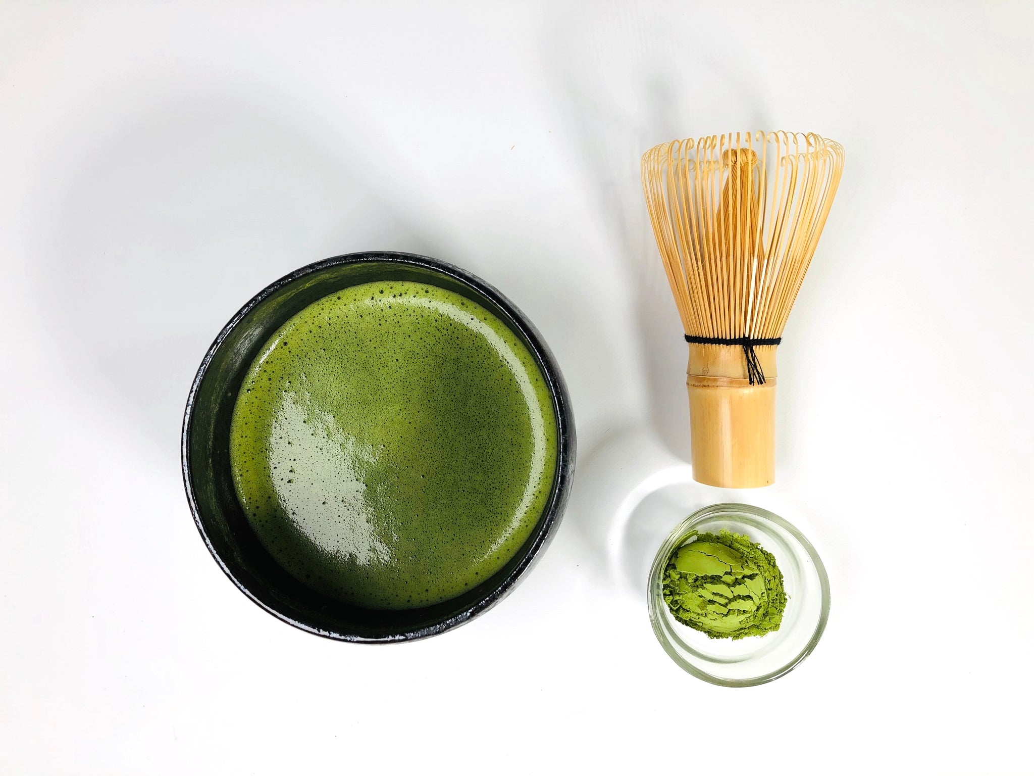 prepared matcha in bowl with matcha whisk and powdered matcha