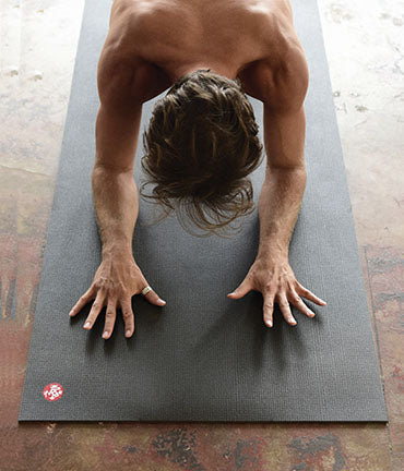 Man doing yoga on a black yoga mat