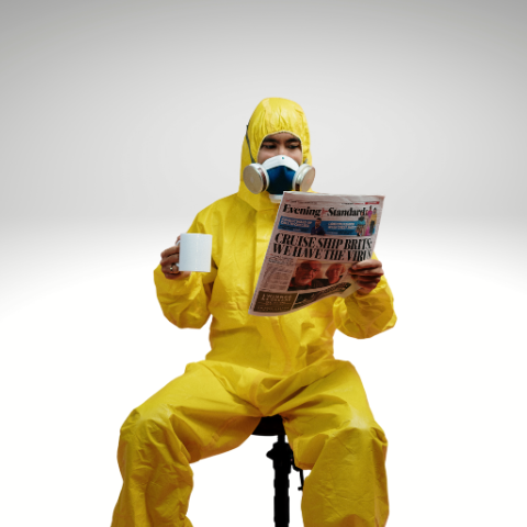 Man sitting in hazmat suit drinking coffee and reading paper