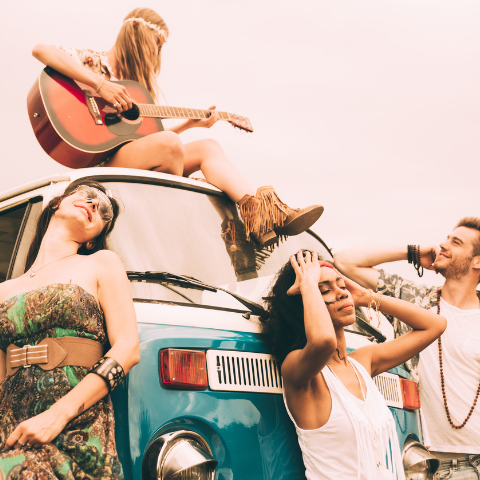 A group of hippie chic friends playing music in a meadow while one girl sits on the car.