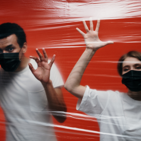 Man and woman wearing face masks behind plastic wrap