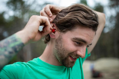Man putting EarPeace in ears on construction site