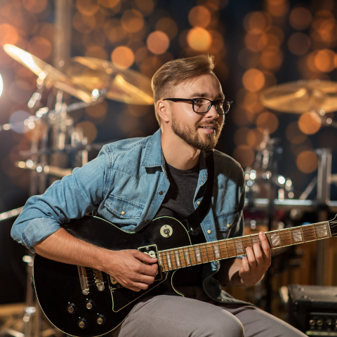 Man with glasses playing guitar