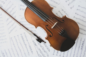 overhead picture of a violin facing diagonally with bow, on top of a pile of sheet music