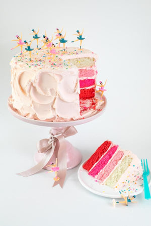 Vintage-inspired toy ballerinas dancing on top of a pink ombre cake sprinkled with Toyland Sprinkles.