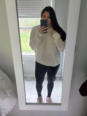 woman standing in front of mirror taking selfie in cream chic sweater and black leggings