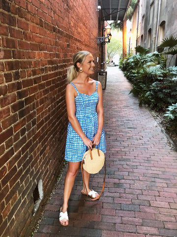 woman in plaid dress with boho bag in front of brick wall