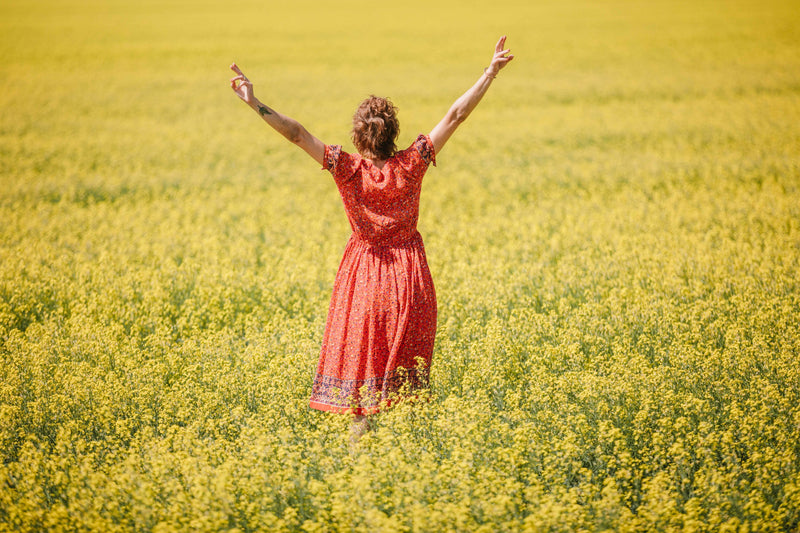 woman in bohemian red dress celebrating in field of flowers