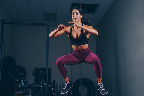 woman jumping while working out in purple leggings