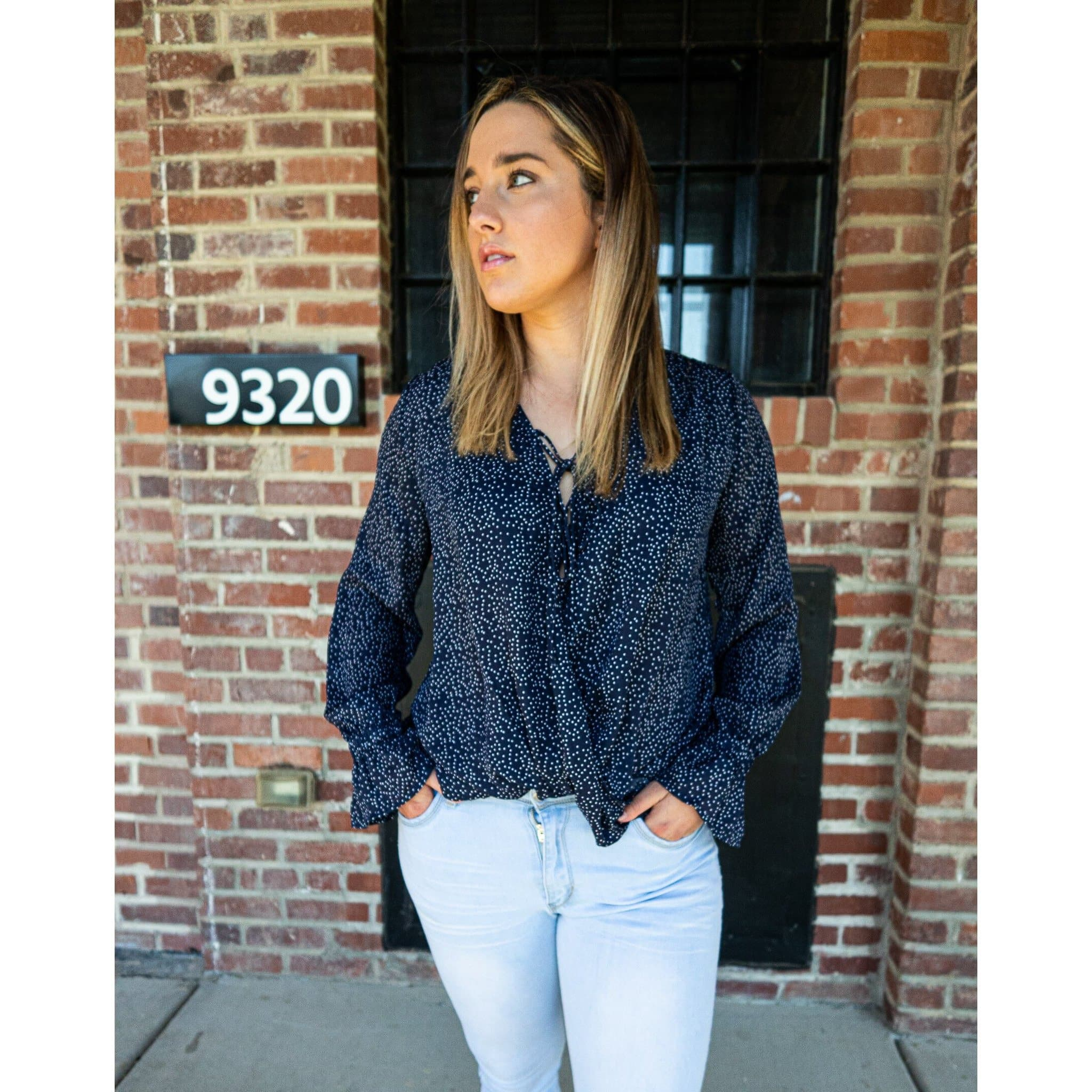 cassie navy blue polkadot blouse with flowy sleeves, lace-up front, and a flowing bodice. trendy, casual top for women. summer and spring fashion for women