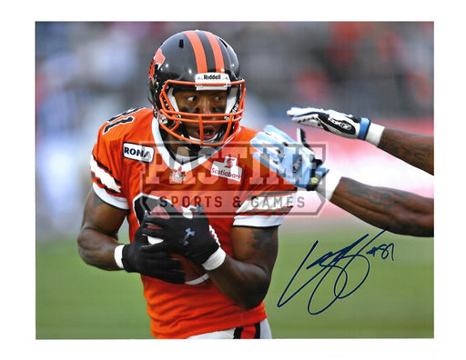 Geroy Simon Autographed 8X10 B.C Lions Home Jersey (Protecting Ball) - Pastime Sports & Games