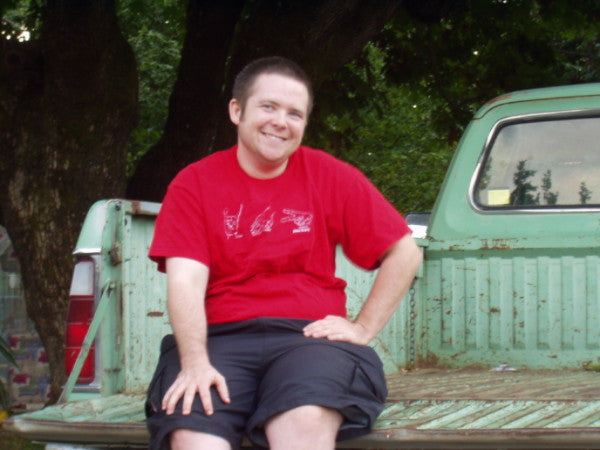 Austin smiling, sitting on a truck 'Austin Unbound'