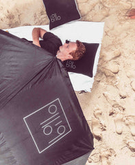 lying on sand with billo under head with billo umbrella
