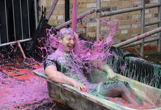 Man sat in a bathtub with purple slime being thrown over him to raise money for charity