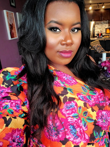 Black woman with long hair taking a selfish in a colorful pink, orange and yellow floral dress