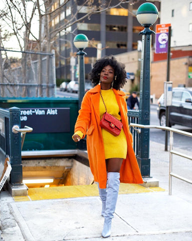 black woman in yellow sweater dress with orange trench coat and cream thigh high boots