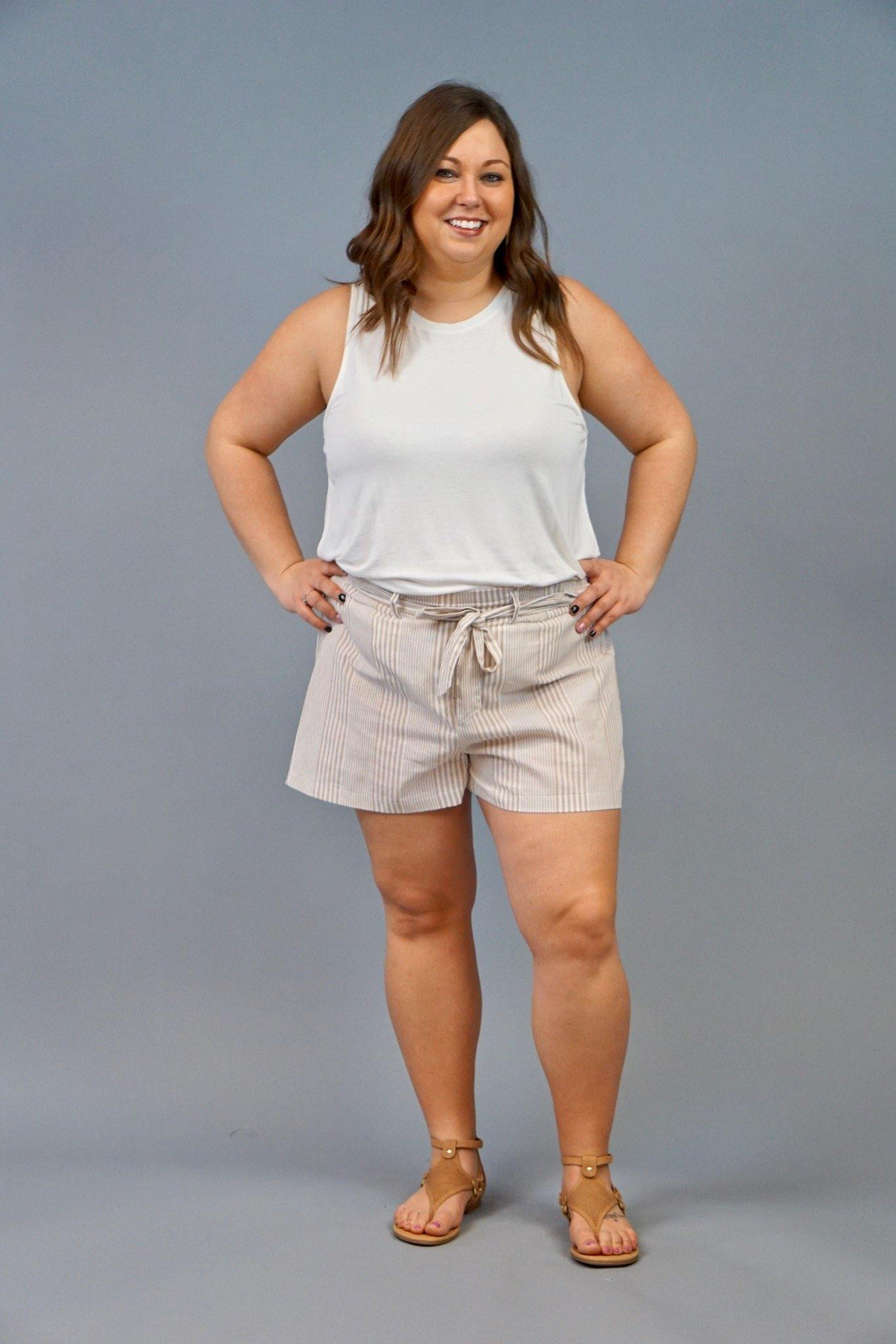 The Hamptons are calling your name!  These shorts are your perfect formal summer shorts.  These shorts are lightweight, khaki and white striped shorts.  They feature a paper bag waist and tie accent.  These shorts are very versatile and can also be dressed down with a Sara Bodysuit for a comfy daytime look.  The Local Online Plus Size Boutique.  The Local Online Curvy Boutique.  Curvy Shorts.  Plus Size Shorts.  Plus Size Paperbag shorts.  Curvy paperboy shorts.