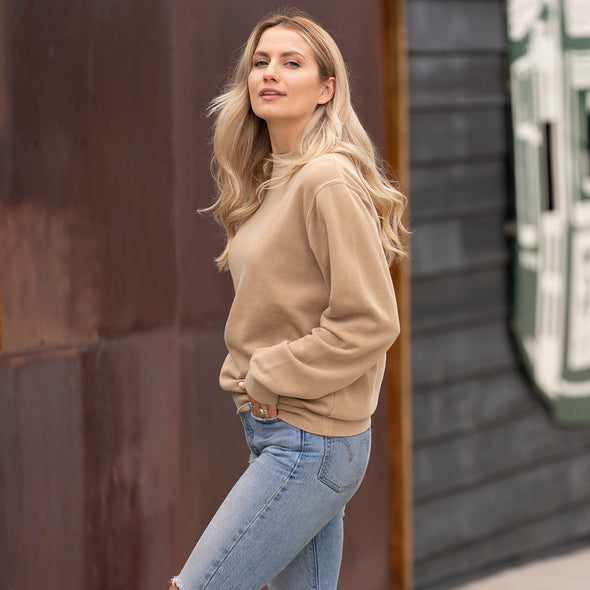 Woman poses in a tan crew neck sweatshirt and blue jeans.