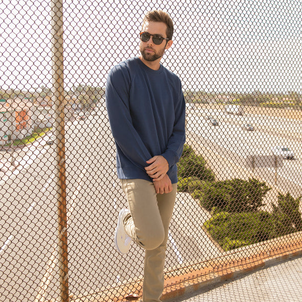 A man stands on a bridge in a navy blue crew neck sweater.