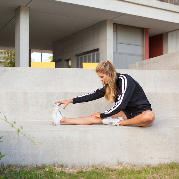 A woman is sitting down and stretching on the steps in front of a building and she is wearing a black track jacket with two vertical white stripes along the sleeves.