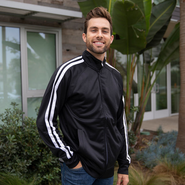 A man poses in front of a building and he is wearing a fully zipped up black track jacket with two vertical stripes along the sleeves.