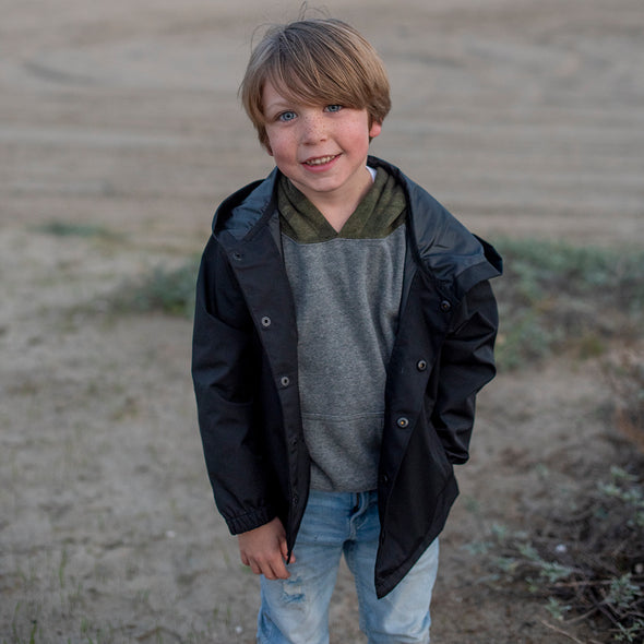 Boy poses on the beach wearing a black rain jacket.