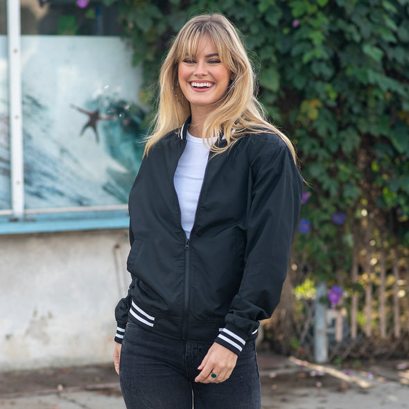 A woman is posing while wearing a black and white bomber jacket.