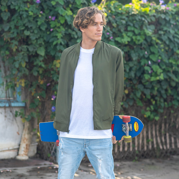 A man is holding a skateboard and wearing an army green bomber jacket over a white t-shirt.