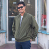 A man is posing in front of a store while wearing an army green bomber jacket and sunglasses.