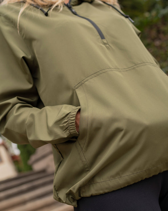 Close up of an army green windbreaker, highlighting its elastic cuffs and kangaroo pocket.