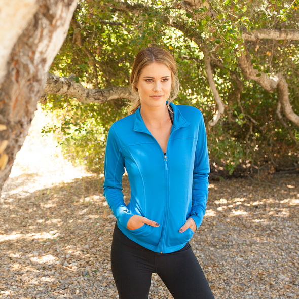 Woman poses under a tree in a blue yoga jacket.