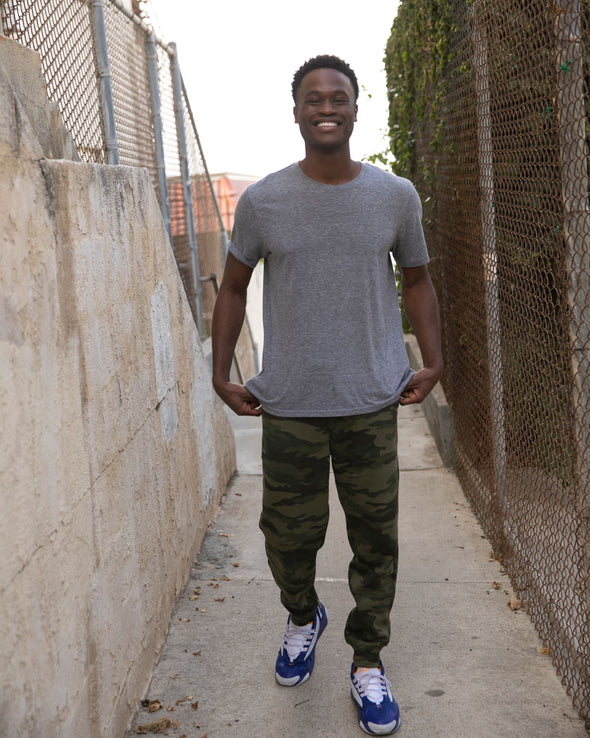 Man is posing in alley wearing a gray t-shirt and green camouflage sweatpants.