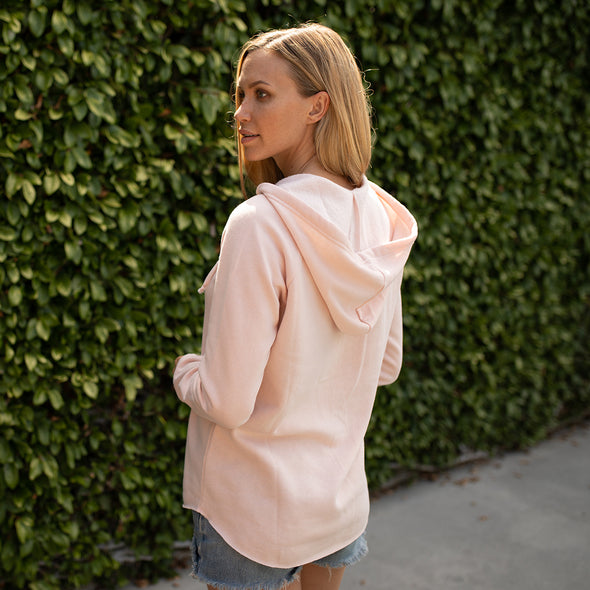 Woman poses in a pastel pink pullover hoodie.