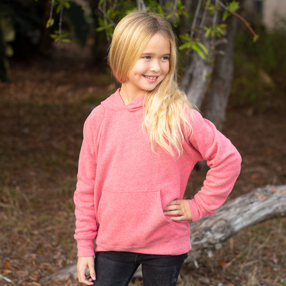 Girl poses in a pomegranate pink pullover hoodie and black jeans.