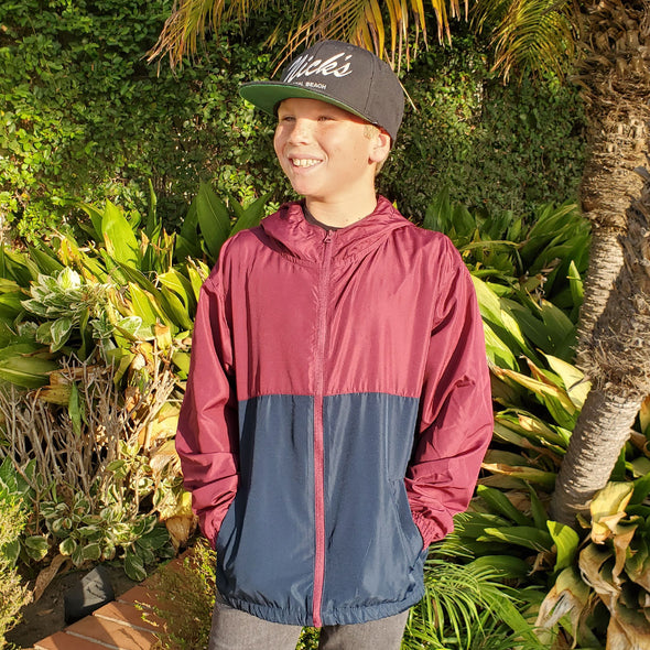 A boy is wearing a maroon and navy windbreaker hoodie in front of plants and foliage.