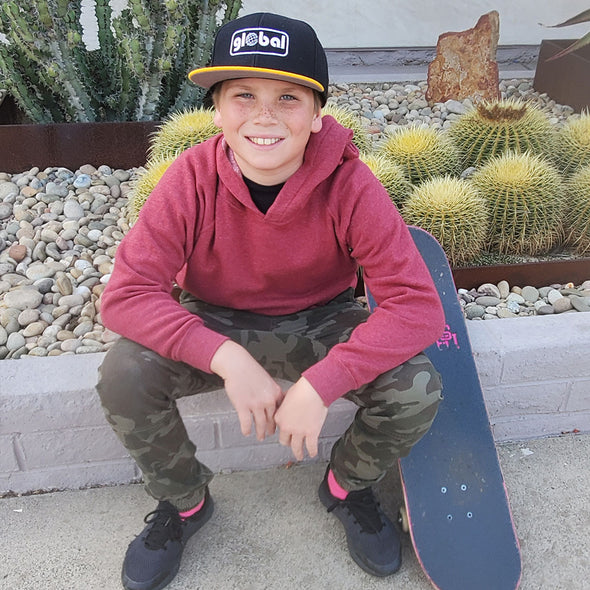 Boy sits on a curb with a skateboard and he is wearing a maroon pullover hoodie and green camouflage pants.