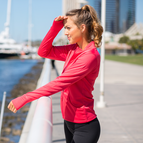 Woman looks away and is wearing a coral pink yoga jacket.