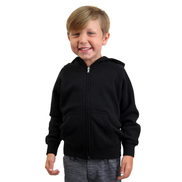 Boy poses in front of a white background and is wearing a black zip-up hoodie.