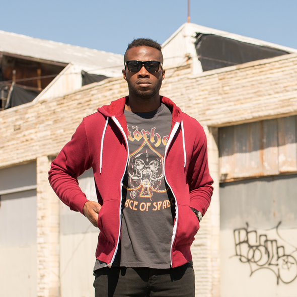 A man poses in a t-shirt and an unzipped burgundy hoodie.