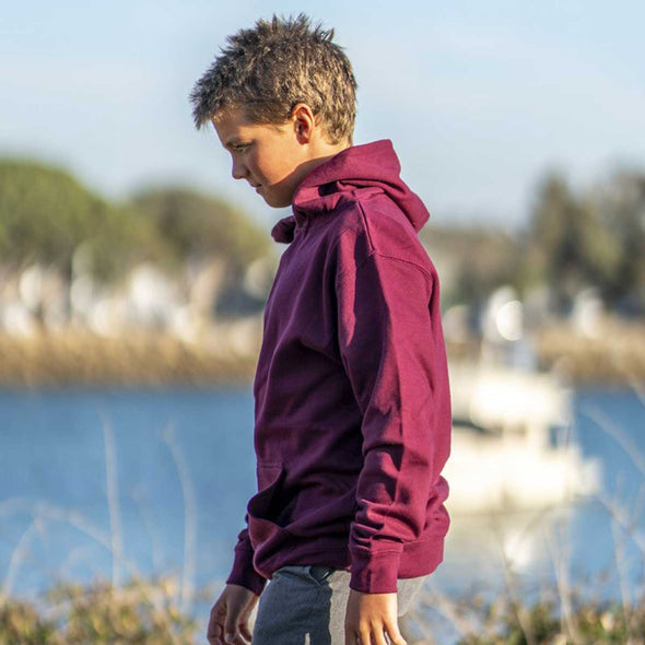 Boy walks in front of lake and he is wearing a maroon pullover hoodie.