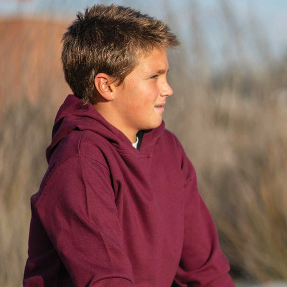 Close up of boy wearing a maroon pullover hoodie.