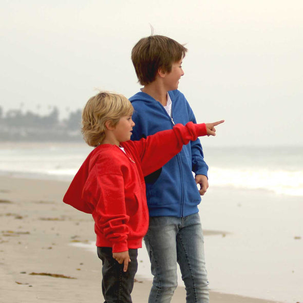Two boys standing on the beach, looking out into the ocean. The boy on the right is wearing a blue hoodie and the boy on the left is wearing a red hoodie.
