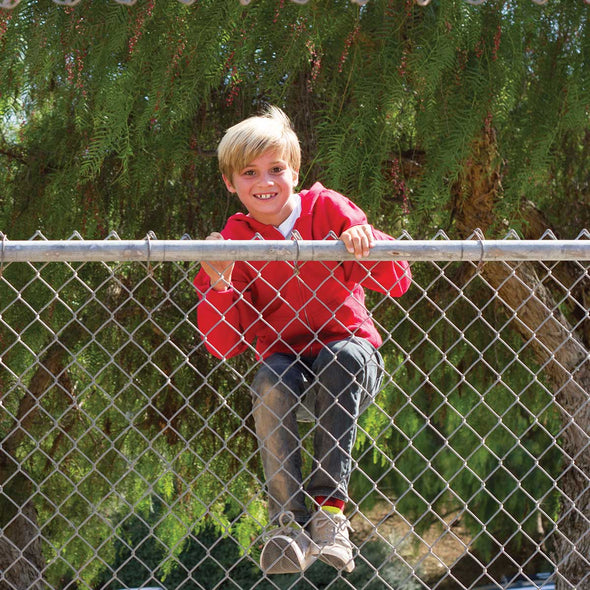 A boy is climbing a fence and he is wearing a red hoodie.