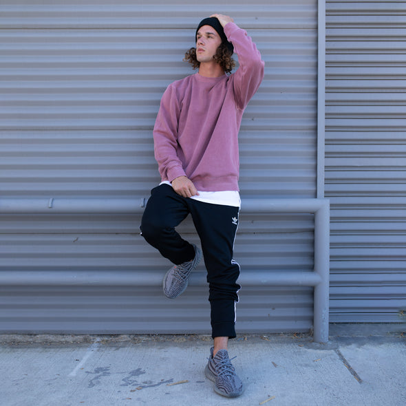 Man poses in a pastel maroon crew neck sweatshirt.