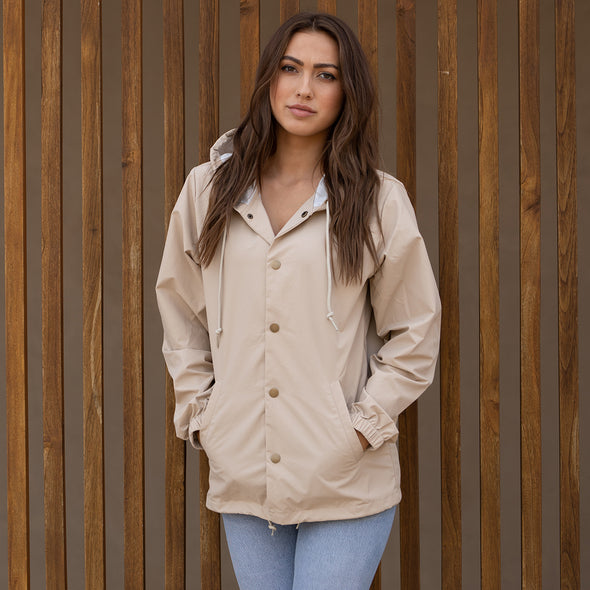 Woman poses in a khaki hooded coach's jacket.