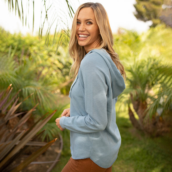 Woman poses in a pastel blue pullover hoodie.