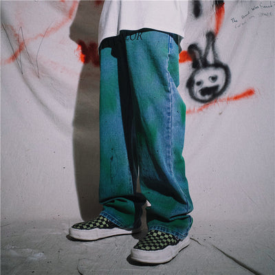 Distressed graffiti spray painted jeans in green