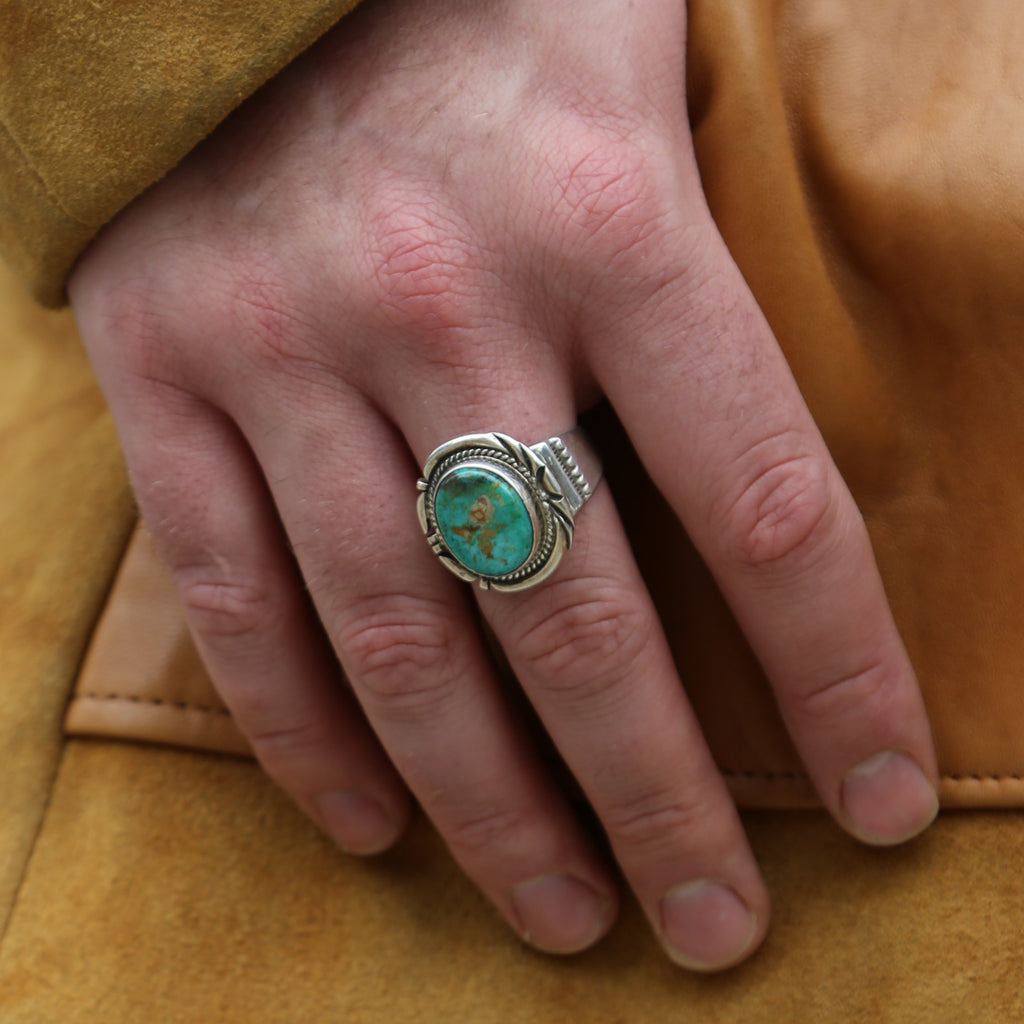"A vibrant turquoise ring stamped by artist ""J.Nelson""."