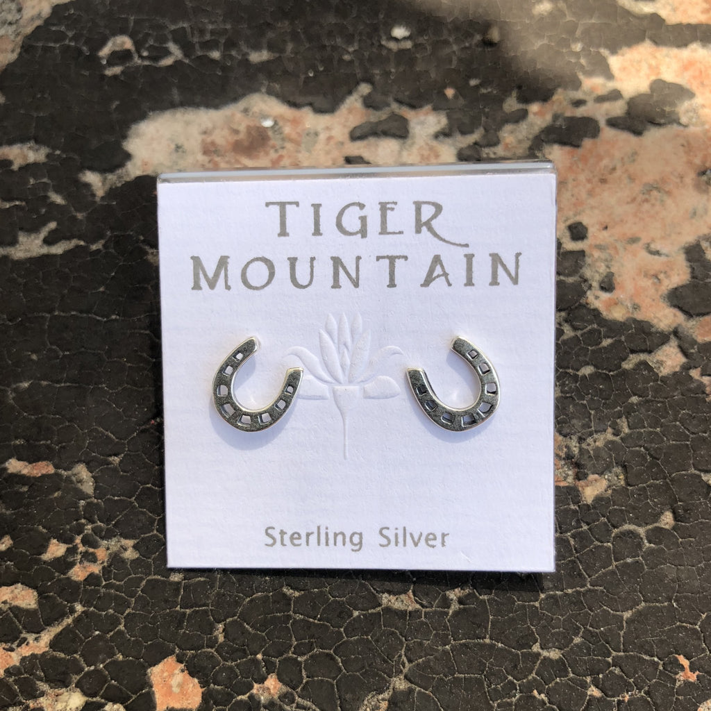 These western horseshoe stud earrings were made by Tiger Mountain. These western rodeo cowgirl earrings are made using sterling silver.