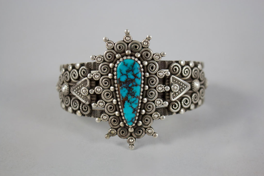 This beautiful turquoise cuff is made with intricate metal designs and features an iconic turquoise stone in its center. Made by artist, Wendell Howard. This piece is included in our estate jewelry collection.